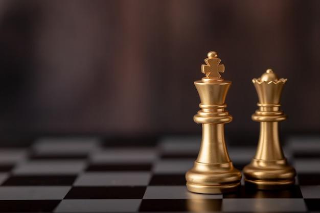 Gouden koning en koningin op het bord