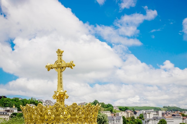 Gouden kruis en kroon op de blauwe hemelachtergrond in lourdes frankrijk