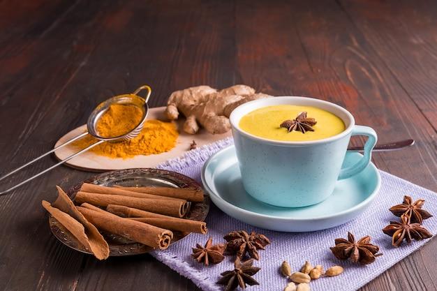 Gouden kurkuma latte melk gemaakt met kurkuma en kruiden op houten achtergrond
