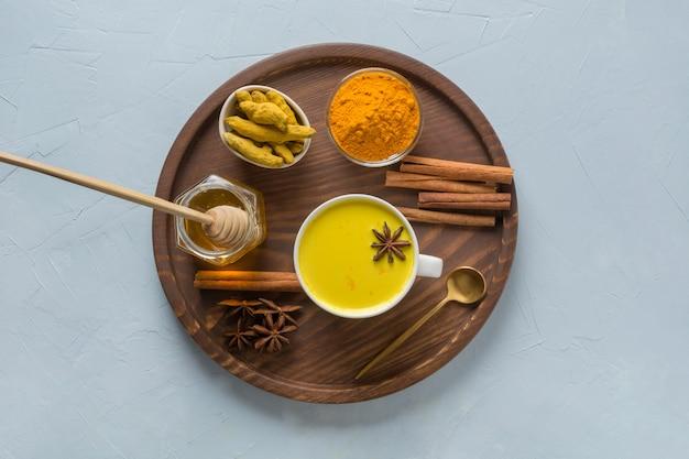 Gouden kurkuma melk met kurkuma poeder, honing en kruiden op lichtblauw. gezond drankje voor immuniteit. uitzicht van boven.