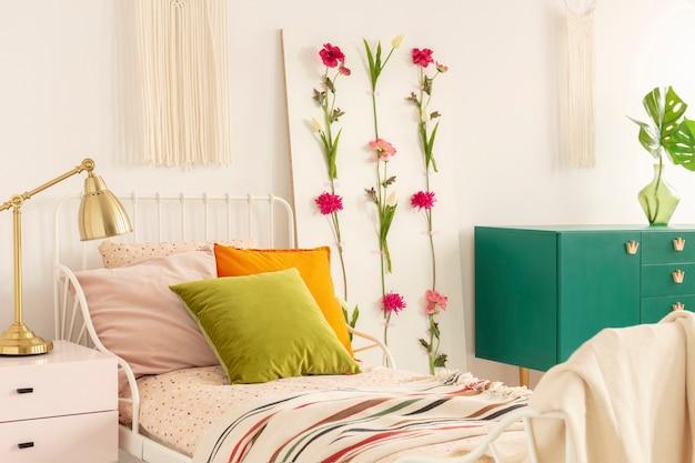 Gouden lamp op pastelroze nachtkastje naast eenpersoons metalen bed met olijfgroen oranje
