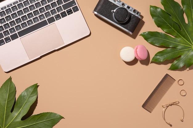 Gouden laptop op beige achtergrond met groene bladeren. schoonheid vrouw blog. bovenaanzicht, plat gelegd. bureau aan huis.