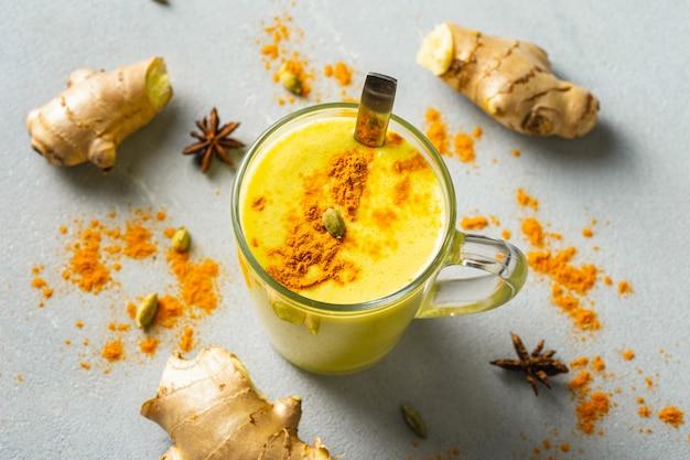 Gouden latte. indiër drinkt kurkuma gouden melk in glas