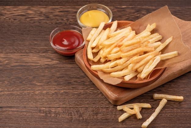 Gouden lekkere diepe frietjes op kraft bakpapier en dienblad om te eten met ketchup en gele mosterd, bovenaanzicht, levensstijl.