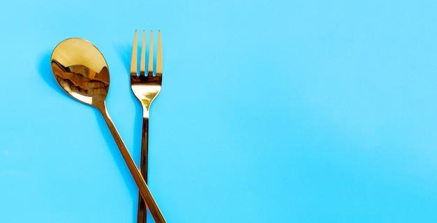 Gouden lepel en vork op blauwe achtergrond.