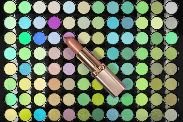 Gouden lippenstift op de kleurrijke achtergrond van het oogschaduwpalet. plat leggen. bovenaanzicht