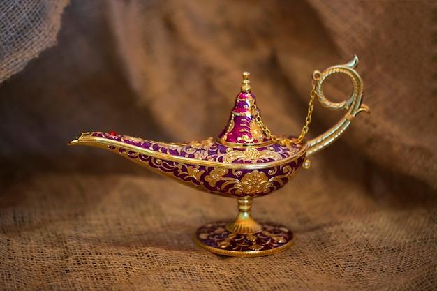 Gouden magische geest lamp op jute, close-up. lamp van verlangens uit het verhaal van aladdin met genie