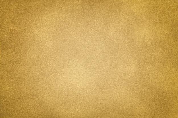 Gouden matte suède stoffenclose-up. fluwelen textuur achtergrond
