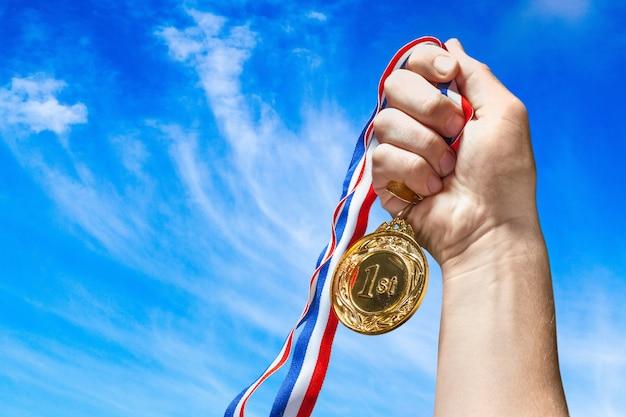 Gouden medaille met lint in de hand op achtergrond