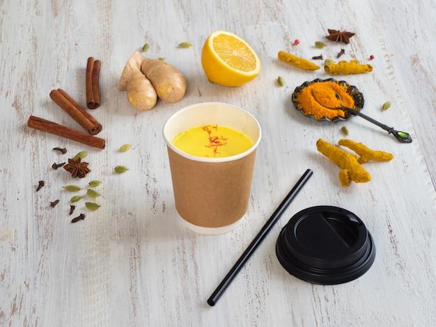 Gouden melk in een papieren beker met kurkuma, kaneel, gember, citroen en peper. preventie van antivirale infecties