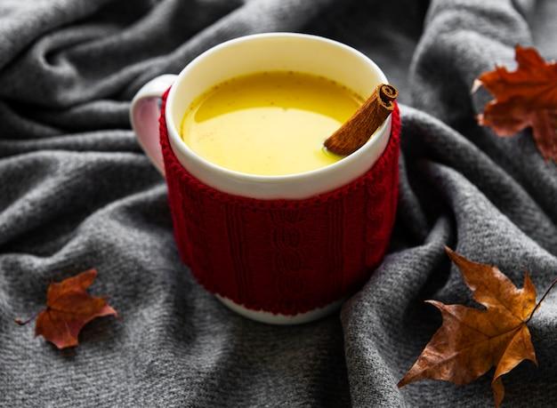 Gouden melk in een witte kop. herfstbladeren. een gezonde drank gemaakt van melk, kurkuma, kaneel en honing.