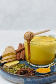 Gouden melk in glaskop met kruiden over dichte omhooggaand. honing stroomt in een kopje.
