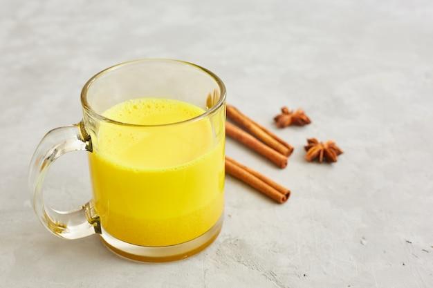 Gouden melk met kurkuma in een transparante beker, anijs sterren en kaneelstokjes. gezond eten concept.
