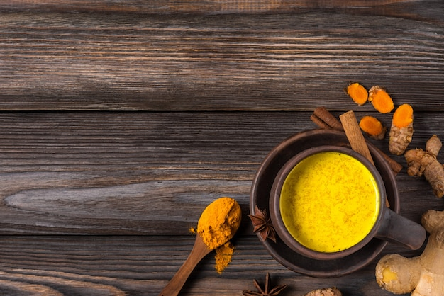 Gouden melk of kurkuma latte gemaakt met kurkuma, steranijs, gember en kaneel op rustieke houten tafel. bovenaanzicht