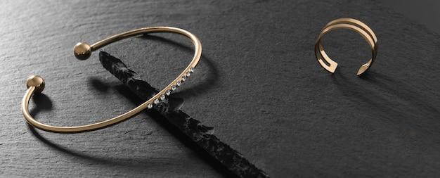 Gouden moderne armband met diamanten en gouden ring op zwarte stenen platen