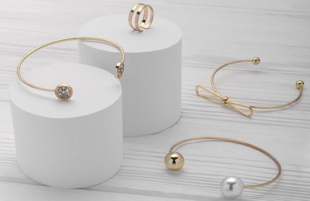 Gouden moderne armbandeninzameling en ring op witte platforms op houten achtergrond