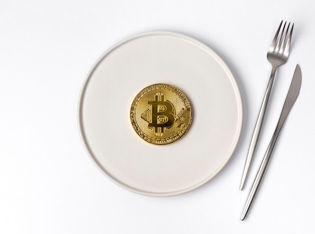 Gouden munt bitcoin geserveerd op witte lege plaat