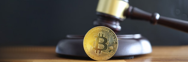 Gouden munt bitcoin liggend naast rechter hamer close-up