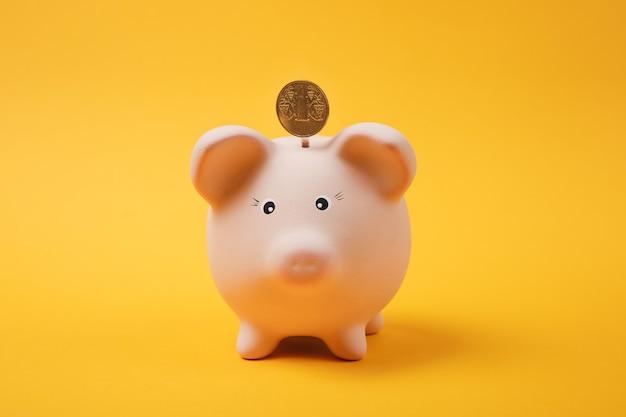 Gouden munt die in roze spaarvarken valt dat op heldere gele achtergrond wordt geïsoleerd. geldaccumulatie, investeringen, bank- of zakelijke diensten, rijkdomconcept. kopieer ruimte reclame mock-up.