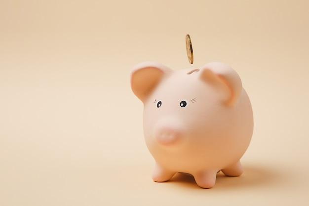 Gouden munt vallen in roze spaarvarken geïsoleerd op pastel beige achtergrond. geldaccumulatie, investeringen, bank- of zakelijke diensten, rijkdomconcept. kopieer ruimte reclame mock-up.