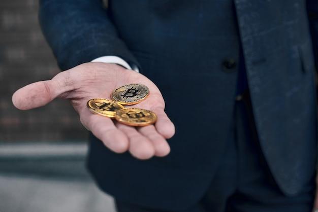 Gouden munten bitcoin gestapeld in de handpalmen van een jonge vrouw