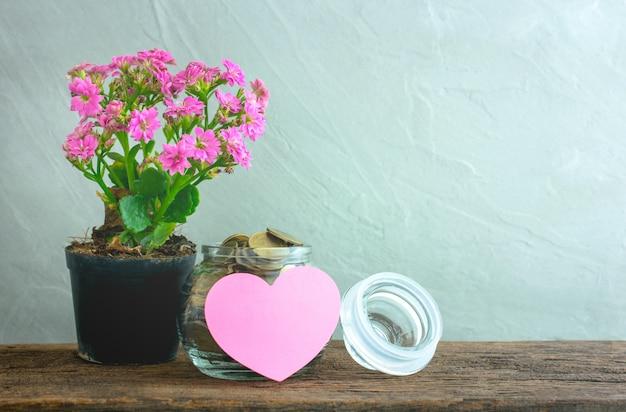 Gouden munten in een glazen pot met hart papier opmerking over houten tafel