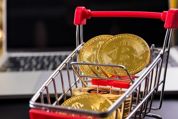 Gouden munten met bitcoin symbool in een klein winkelwagentje met computer achtergrond.