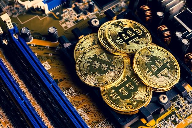 Gouden munten met bitcoin symbool op een moederbord.