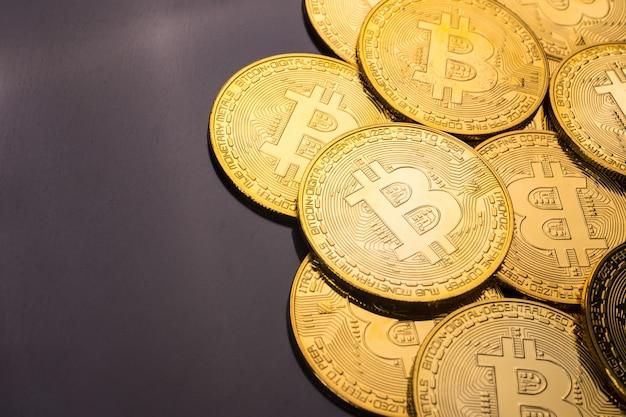 Gouden munten met bitcoin symbool op een zwarte achtergrond.