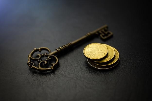 Gouden munten met sleutel, sleutel tot geld, om donkere achtergrond