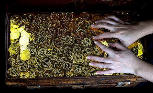 Gouden munten stapelen in schatkist op zwarte achtergrond