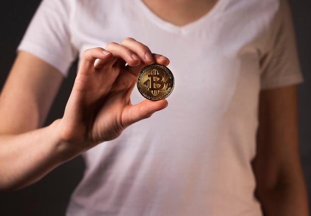 Gouden muntstuk van btc of bitcoin gehouden bu vrouwelijke hand.