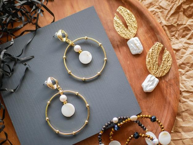Gouden oorbellen. dames sieraden. vintage decoratie achtergrond. mooie gouden tinten broches, armbanden, kettingen en oorbellen op een houten dienblad. plat lag, bovenaanzicht