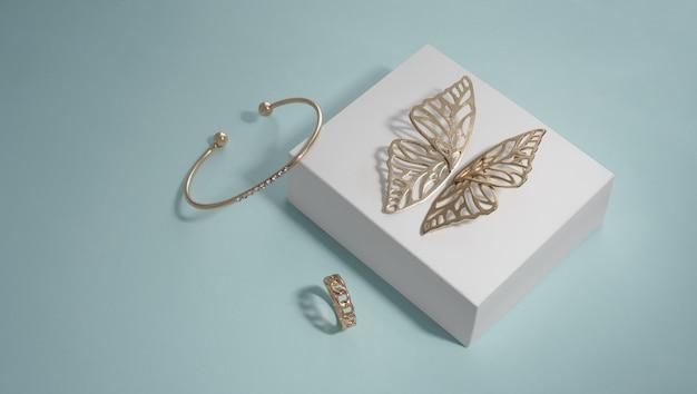 Gouden oorbellen en armband in de vorm van een vlinder op een witte doos met een ring in de vorm van een ketting op een blauwe achtergrond