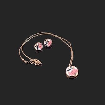 Gouden oorbellen en gouden ketting met email op donker reflecterend oppervlak