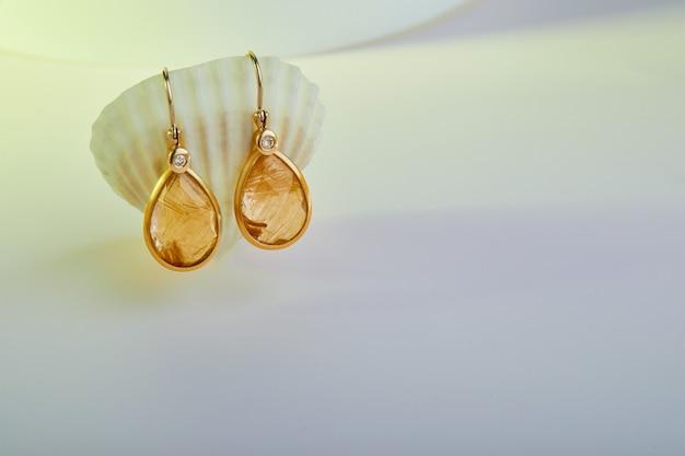 Gouden oorbellen op een zeeschelp