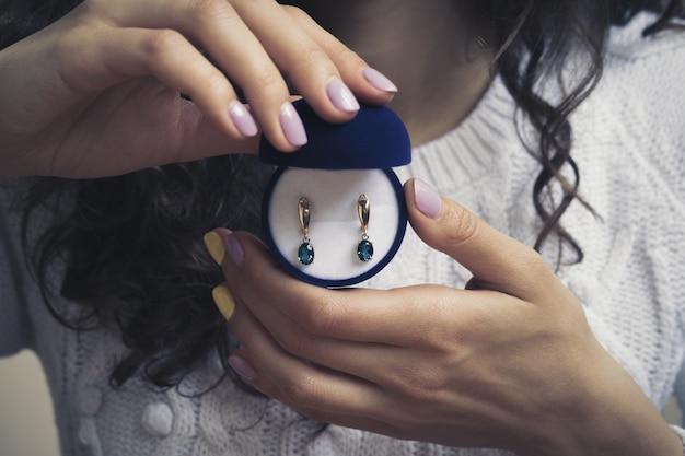 Gouden oorringen met blauwe topaas in de handen van vrouwen