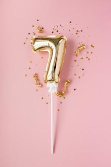 Gouden opblaasbaar nummer 7 op een stokje gouden confetti op een roze achtergrond. concept van een vakantie, verjaardag, jubileum.