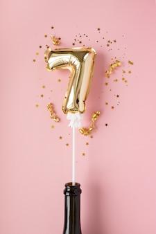 Gouden opblaasbaar nummer 7 op een stokje in een champagnefles omringd door lovertjes op een roze achtergrond.