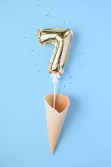 Gouden opblaasbaar nummer 7 op een stokje in een wafelkegel omgeven door lovertjes op een blauwe achtergrond. het concept van een vakantie, verjaardag of jubileum.