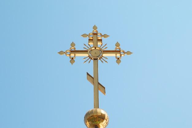 Gouden orthodox kruis met blauwe hemelachtergrond