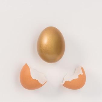 Gouden paasei ging uit ei met gebroken schaal.