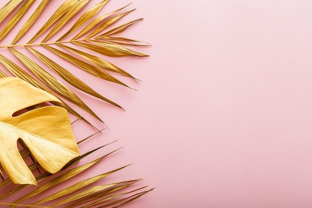 Gouden palmblad, tropisch verlofframe op roze achtergrond met copyspace. zomer pagina gouden bloemen frame. plat leggen.