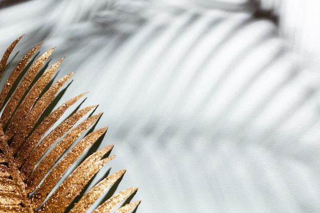 Gouden palmbladeren en schaduwen op een blauwe muurachtergrond.