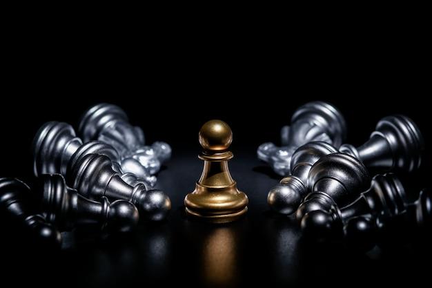 Gouden pandschaak die door een aantal gevallen zilveren schaakstukken, bedrijfsstrategieconcept wordt omringd