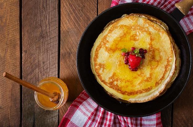 Gouden pannenkoeken met cranberry jam en honing in een rustieke stijl. bovenaanzicht