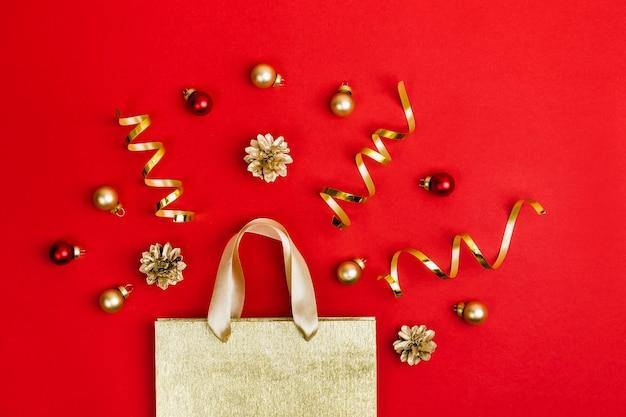 Gouden papieren boodschappentas, kegels, serpanin en ballen op rode achtergrond. kerst verkoop concept.