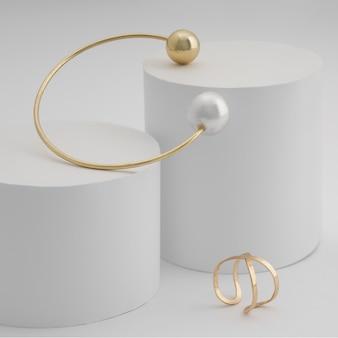 Gouden parelarmband en ring op witte blokken