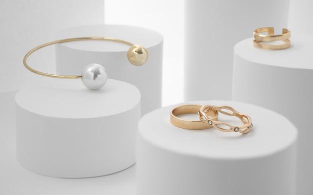 Gouden parelarmband en ringen op witte papieren cilinders