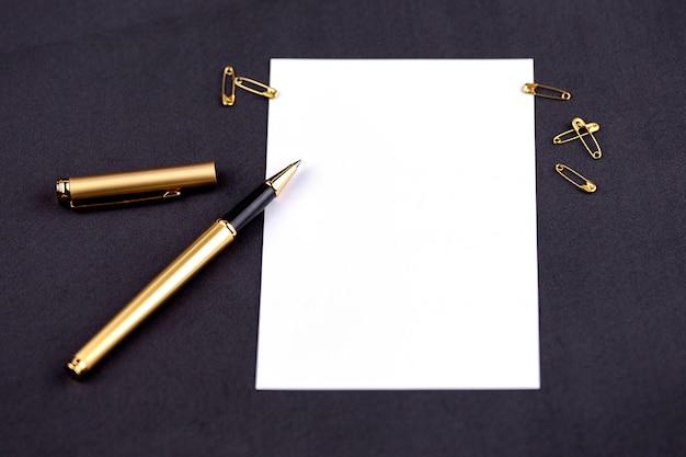 Gouden pen, lint, paperclips en briefpapier op een zwarte achtergrond met een wit vel papier met kopie ruimte